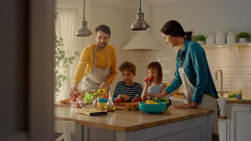 In the Kitchen: Family of Four Cooking Together Healthy Dinner. Mother, Father, Little Boy and Girl, Preparing Salads, Washing and Cutting Vegetables. Cute Children Helping their Caring Parents Royalty-Free Stock Footage #1049601256