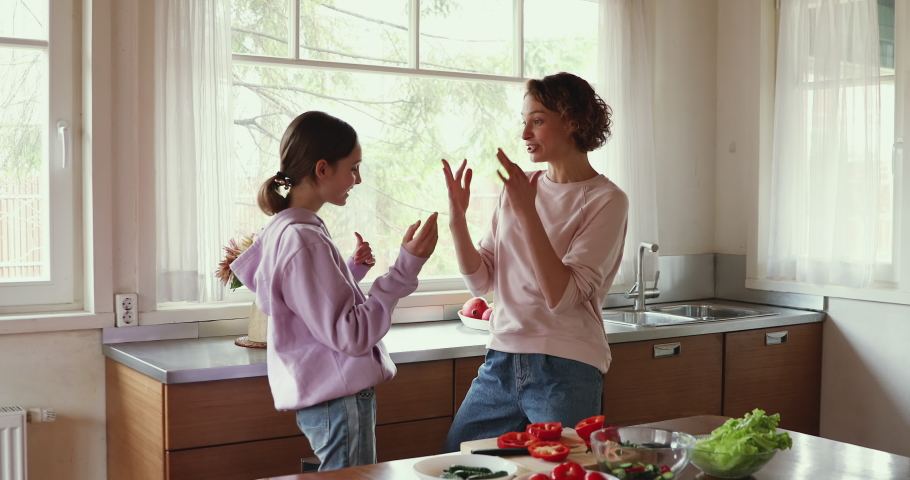 Young happy family mom and teen daughter enjoy funny dance in kitchen cooking together. Cheerful adult parent mother having fun with adolescent teenage girl preparing healthy salad at home together.