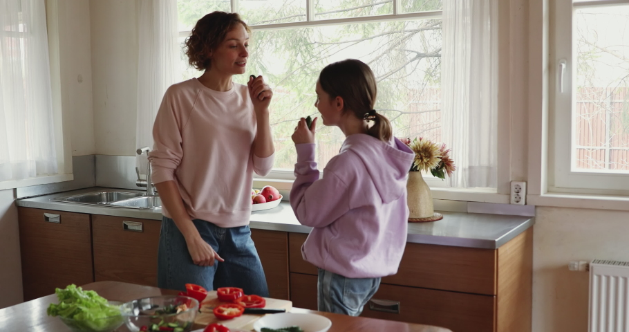 Happy family teenage child daughter and young adult mom holding cucumbers microphones enjoying singing and cooking. Funny mommy having fun with teen kid preparing vegetable salad in kitchen together.
