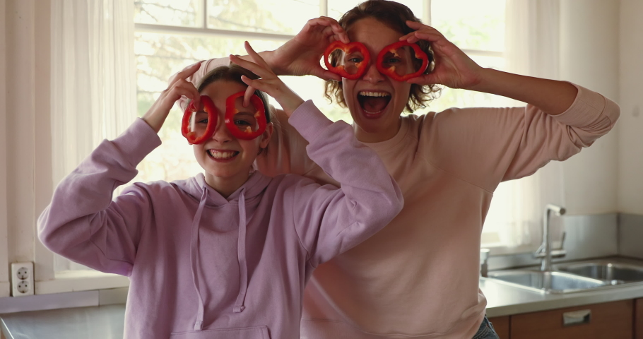 Funny young mom and teenage daughter making pepper glasses having fun. Happy teen girl helping mum in kitchen laughing, looking at camera. Cheerful vegan family enjoying cooking activity, portrait.