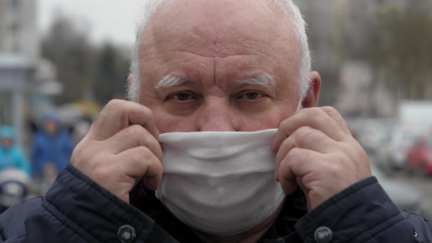 Close up portrait elderly man puts a medical mask on his face to protecting yourself from coronavirus pandemic. Standing on street, people are moving in background. Protection health and safety life. | Shutterstock HD Video #1049609314