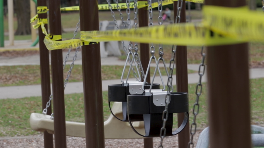 Empty swing set with caution tape to close off playground to children to help fight the coivd-19 disease. Close up empty swing set playground.  | Shutterstock HD Video #1049615428