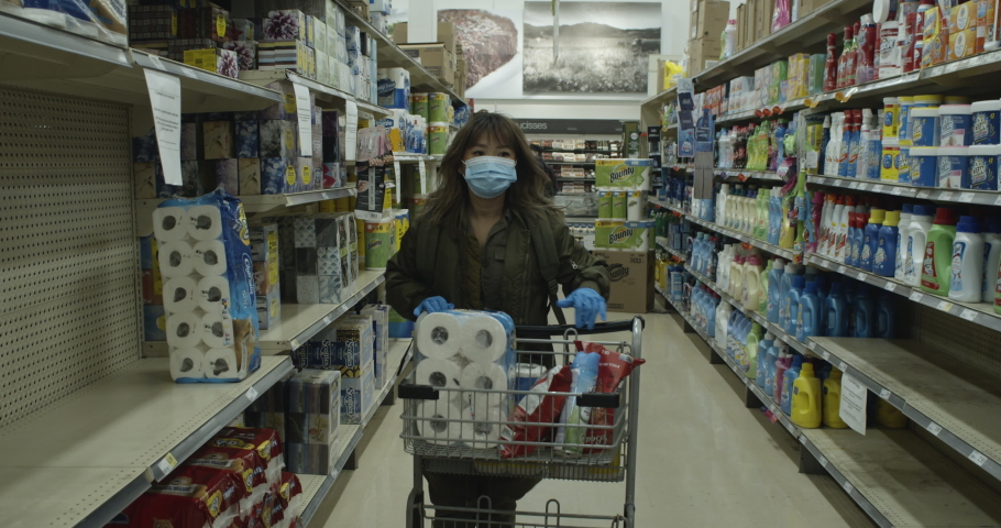 MONTREAL, QUEBEC - MARCH 27, 2020: Shopper walks in grocery style aisle picking up toilet paper from an almost empty shelf during the coronavirus pandemic