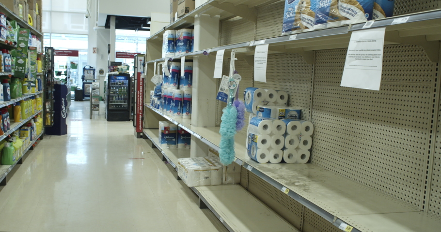 MONTREAL, QUEBEC - MARCH 27, 2020: Grocery store clerk walks by nearly early empty shelves in supermarket with what is left of toilet paper during coronavirus pandemic