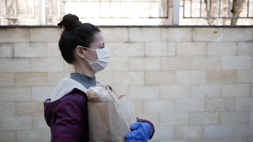 Courier, delivery man in protective mask and medical gloves delivers takeaway food. Delivery service under quarantine, disease outbreak, coronavirus covid-19 pandemic conditions. Stay home.