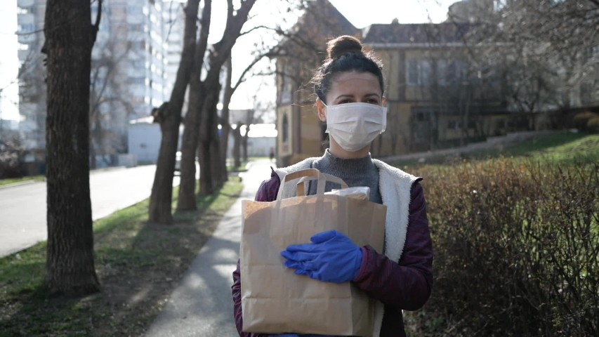 Food delivery young woman in protective mask and gloves carries bag with products from store. pandemic. | Shutterstock HD Video #1049629267