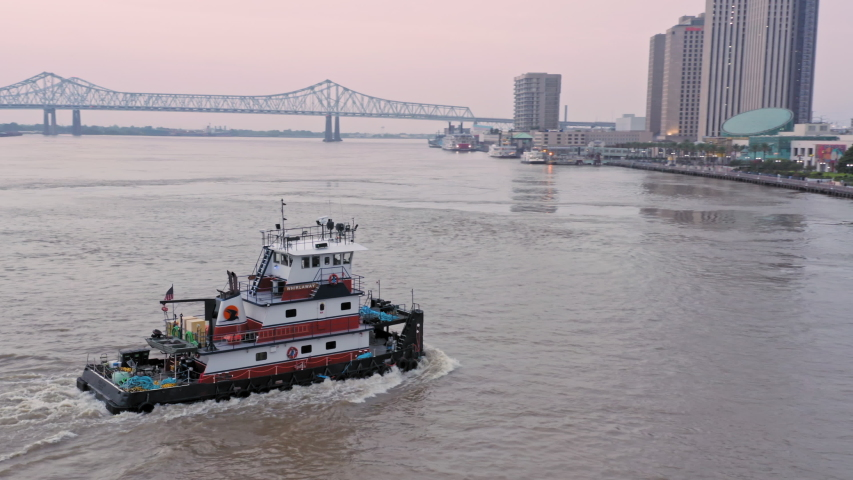 Aerial:Tugboat on the Mississippi River and the city skyline at sunrise New Orleans, Louisiana, USA. 24 June 2019