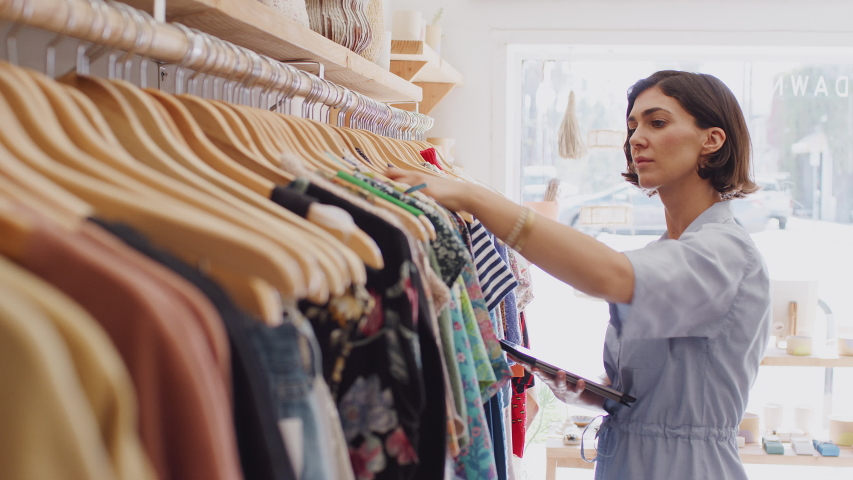 Female owner of fashion store using digital tablet to check stock on rails in clothing store - shot in slow motion Royalty-Free Stock Footage #1049651593