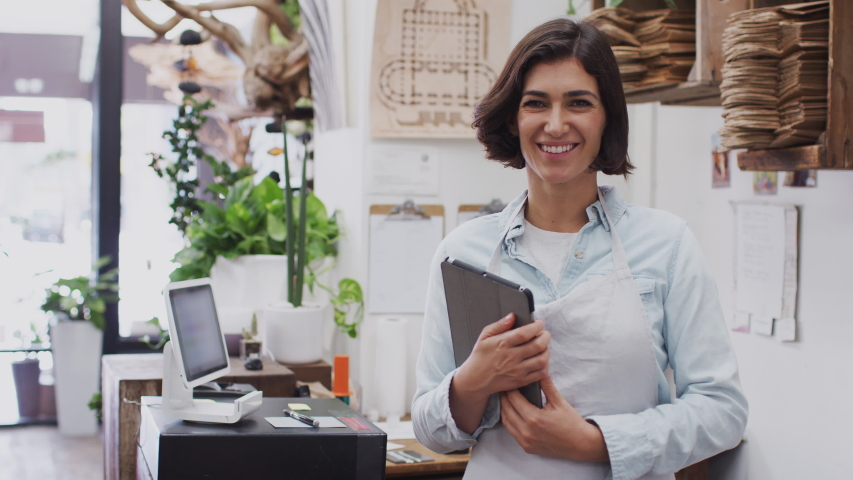 Portrait of female owner of florists shop working on digital tablet behind sales desk - shot in slow motion Royalty-Free Stock Footage #1049651608