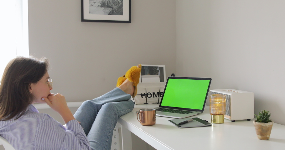 Beautiful young woman watching laptop with green screen, drinking coffee while sitting on the chair in the living room. Feet on the desk. Self isolation, Home quarantine, pandemic people, covid-19 | Shutterstock HD Video #1049655910