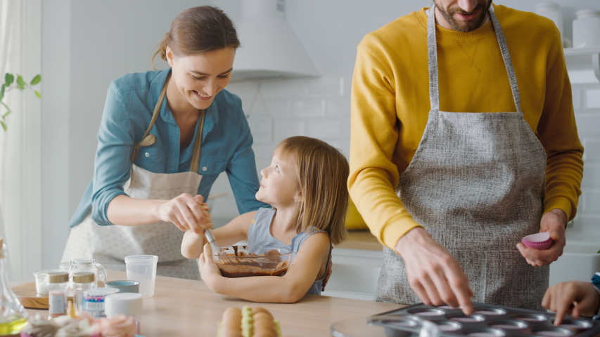 In the Kitchen: Family of Four Cooking Muffins Together. Mother and Daughter Mixing Flour and Water to Create Dough for Cupcakes, Father, Son Preparing Paper Lines for Pans. Children Helping Parents | Shutterstock HD Video #1049665552