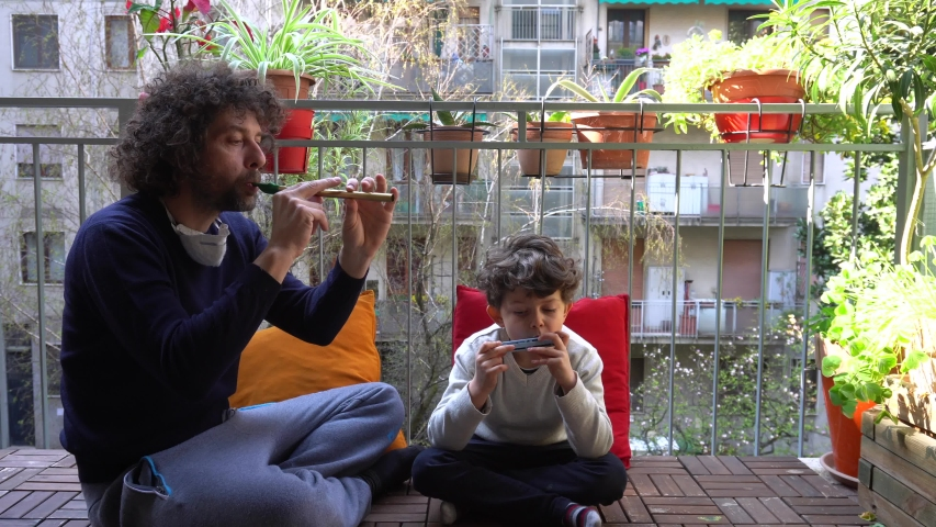 Europe, Italy , Milan - father and son , boy children five years at home during quarantine due n-cov19 Coronavirus outbreak - life stile in apartment - playing music on the balcony - flash mob | Shutterstock HD Video #1049688136