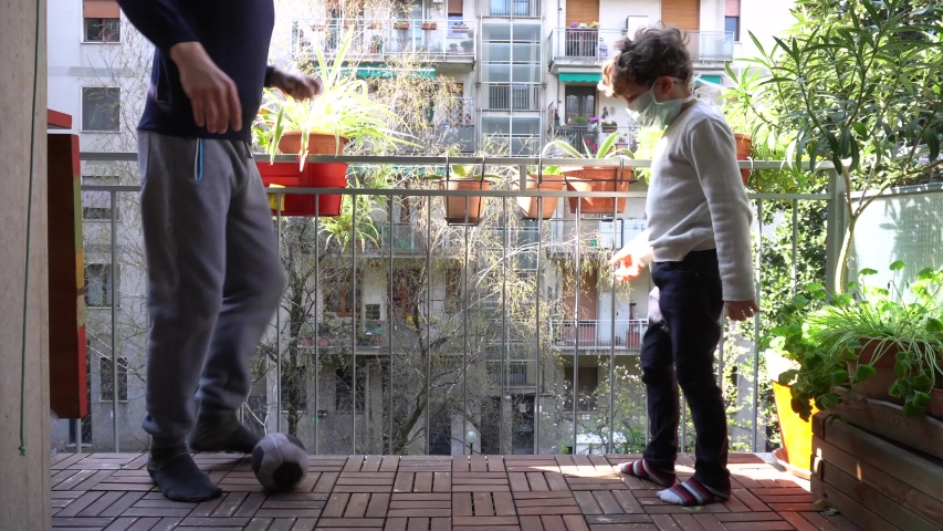 Europe, Italy , Milan - Father and children boy  five years at home during quarantine due n-cov19 Coronavirus outbreak - life stile in apartment - playing soccer football on the balcony #1049688961