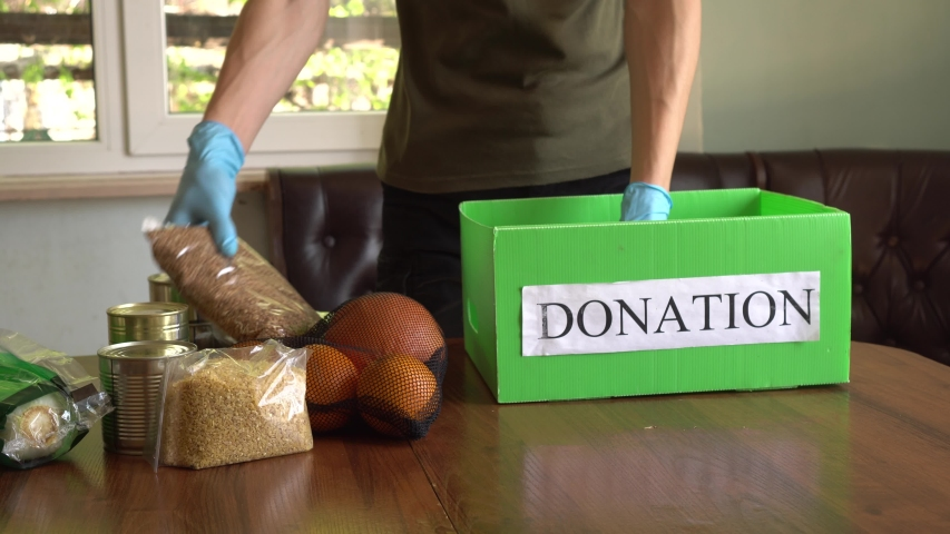 Coronavirus Relief Funds and Donations. Volunteer in the Protective Medical Mask and Hand Gloves Putting Food In Donation Box. Charity donations. Making Donations To Food Bank Royalty-Free Stock Footage #1049689426