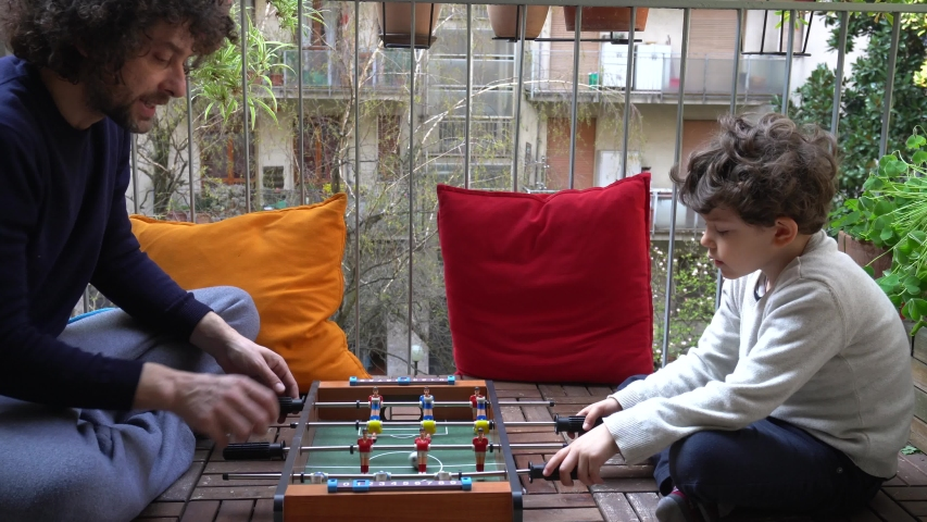 Europe, Italy , Milan - father and son five years at home during quarantine due n-cov19 Coronavirus outbreak - life stile in apartment - Playing soccer football table on the balcony | Shutterstock HD Video #1049690467
