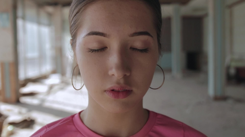 Portrait of young woman, closed eyes. Abandoned hall with panoramic windows, hand held camera | Shutterstock HD Video #1049698114