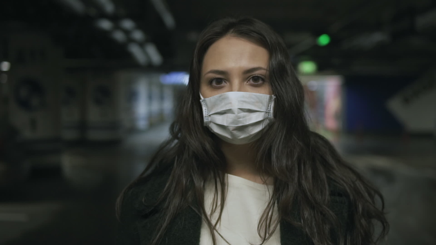Portrait of attractive young woman in protective medical mask, standing alone in empty underground Parking lot during quarantine due to covid-19 coronavirus pandemic, indoors closeup slow motion Royalty-Free Stock Footage #1049705839