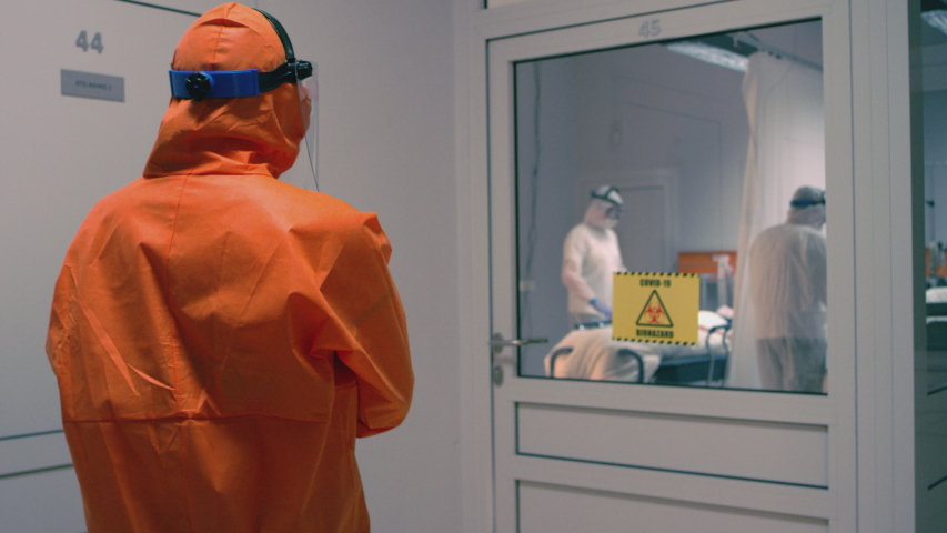 Doctor in an Orange Protective Suit Enters Isolation Room with Coronavirus Patients - Handheld Medium Tracking Shot in Slow Motion | Shutterstock HD Video #1049711419