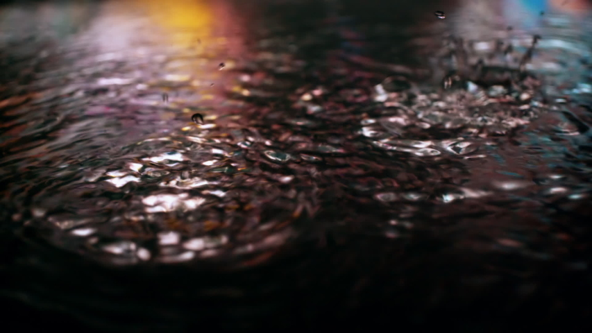 Rain drops falling into puddle on asphalt at night. Big city street lights mirror reflection on water surface. Close-up slow motion of raining outside in wet season