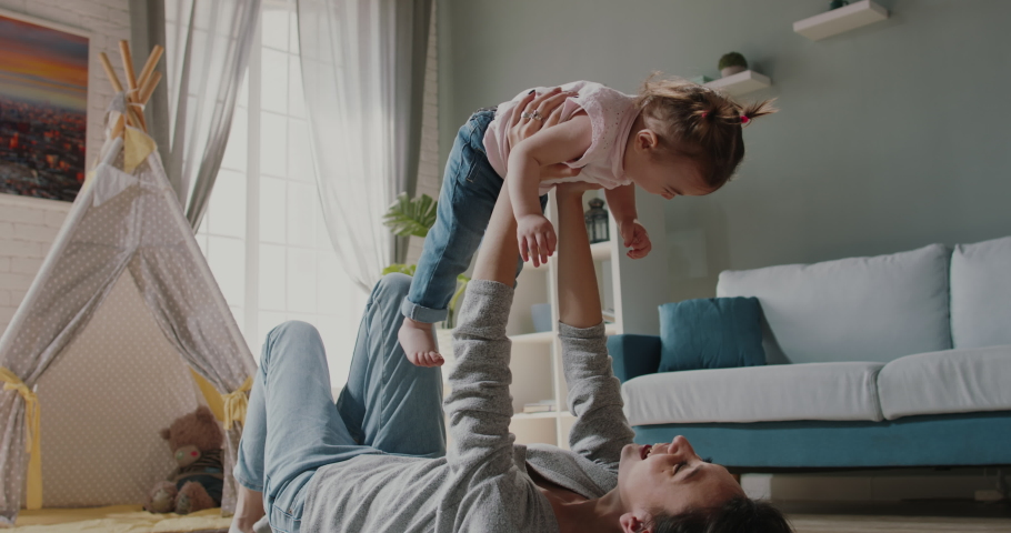 Active caucasian young mom and her little cute daughter playing at home. Joyful babysitter working at home, holding the baby up - happy family, activity together concept 4k footage