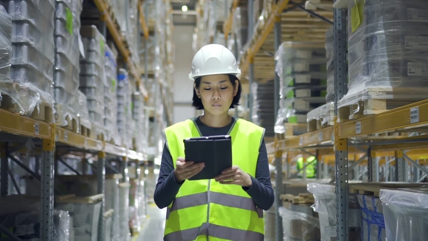 Young asian woman using tablet while walking in warehouse of modern factory. Front view of female employee doing work in storehouse, holding digital device in hand and looking at screen.  Royalty-Free Stock Footage #1049731075