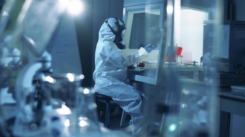 Coronavirus, covid-19, virus research concept. Laboratory worker in protective suit works with covid-19 samples. | Shutterstock HD Video #1049736991