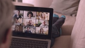 Person Using Video Conferencing technology from sofa for video call with colleagues at home and in offices