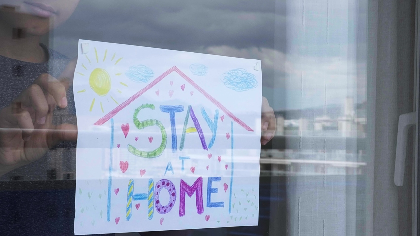 Kid at home sticking to the window glass drawing picture with inscription Stay at home. Social media campaign for coronavirus prevention. Royalty-Free Stock Footage #1049749222