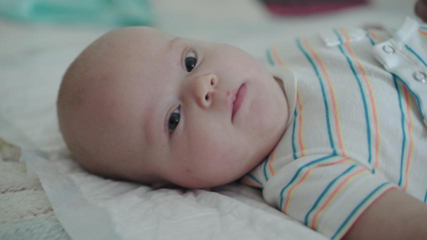 Cute, perplexed babyborn looking at camera and twisting. 4K