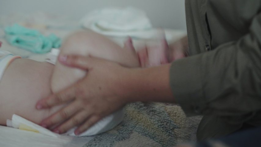 Close unrecognizable view of female hands massaging a babyborn's legs quickly. 4K