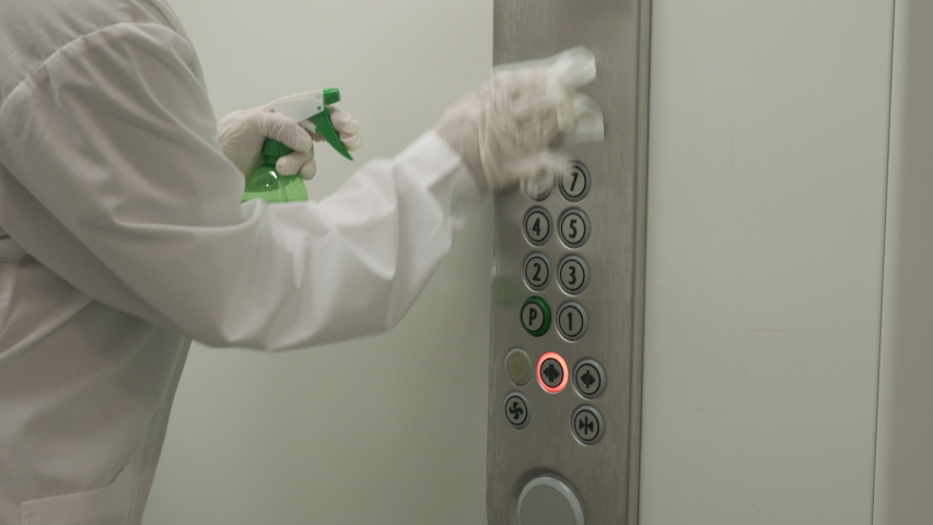Woman using wet wipe and alcohol sanitizer spray to clean an elevator push button control panel. Disinfection, cleanliness and health care, Anti Coronavirus COVID-19 Royalty-Free Stock Footage #1049754790