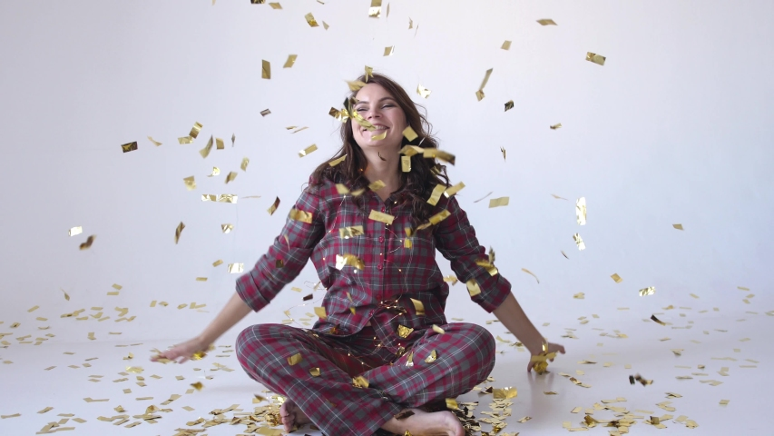 Beautiful happy woman in pajamas sits in studio and throwing gold confetti. slow motion