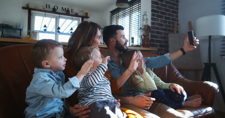 Happy young Caucasian family with three kids wave to friends talking during smartphone video call at home slow motion.