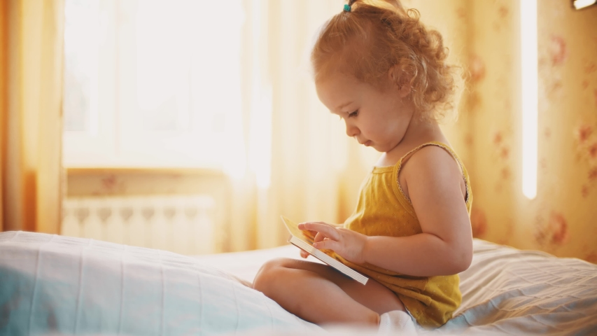 Focused baby girl looks at pictures in the little book in sunny room at home | Shutterstock HD Video #1049758189