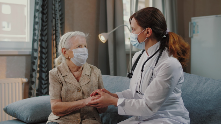 Female nurse talking with elderly woman patient, holds hands. Doctor home visit, checking health of old senior woman during coronavirus, covid-19 quarantine, self isolation. | Shutterstock HD Video #1049767888