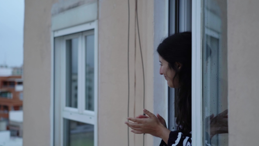Young spanish woman giving an applause to all sanitary staff from her apartment window during quarantine from COVID 19 in Mallorca, Spain | Shutterstock HD Video #1049774029