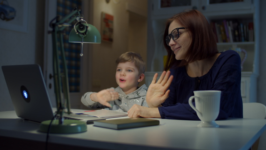 Young 30s mother making online homework with preschooler son at home. Woman in glasses and young boy studying online with laptop and notebook. Online education process.  Royalty-Free Stock Footage #1049780497