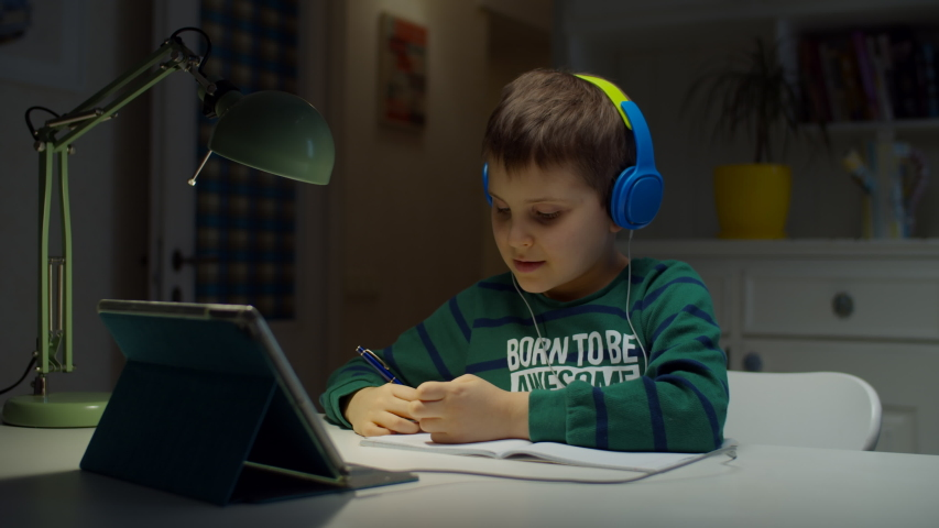 Schooler boy in color headphones using tablet computer for online education at home. Kid enjoys making school homework online, hand writing in textbook.