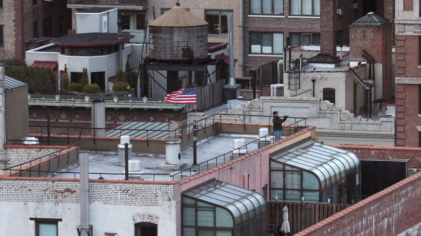NEW YORK, NY, USA - 04 APRIL 2020: Upper West Side New York Man Clapping with American flag on rooftop Cheering Health Care Workers, Health Heroes Coronavirus, Covid-19, Shelter in place, GREAT AUDIO