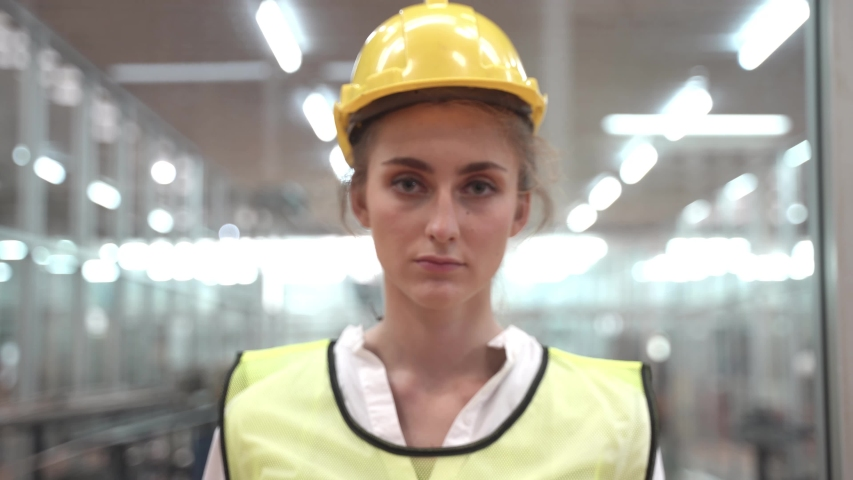 Labor woman worker is wearing protection mask face and safety helmet and wearing suit green reflective safety dress in high tech clean factory. Concept of smart industry worker operating. | Shutterstock HD Video #1049793019