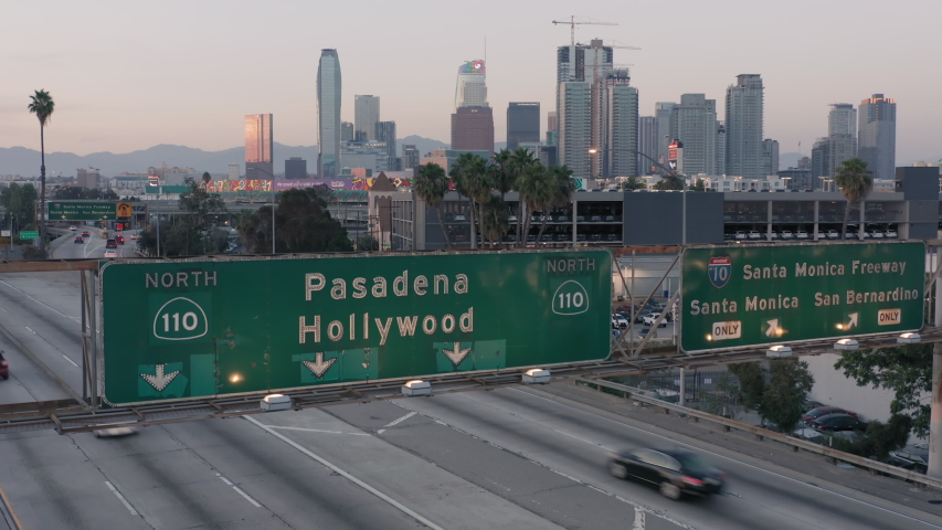 Los Angeles. 2019. Aerial. Drone rises up over the freeway, from the green road sign with Pasadena and Hollywood written on it, to the view of downtown with its skyscrapers and many intersections. 4K