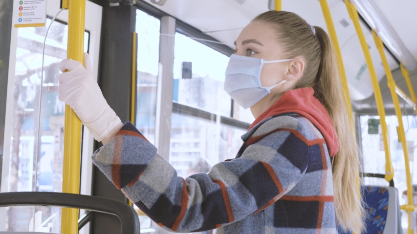 Pandemic COVID-19. A woman in a medical mask rides public transport bus. Prohibition of free movement. Social distance. Coronavirus quarantine in Europe. | Shutterstock HD Video #1049802838