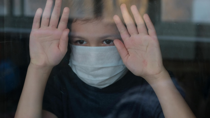 Young boy in a medical mask looks out the window. Self-isolation in quarantine, coronavirus, covid 19. | Shutterstock HD Video #1049809174