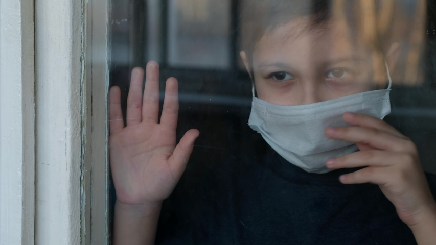 Young boy in a medical mask looks out the window. Self-isolation in quarantine, coronavirus, covid 19.