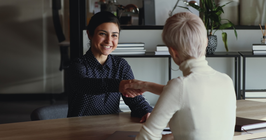 Happy successful indian candidate getting hired after good job interview handshaking female employer. Hr manager employing applicant, selling insurance to client, shaking hand of new company recruit. Royalty-Free Stock Footage #1049816926