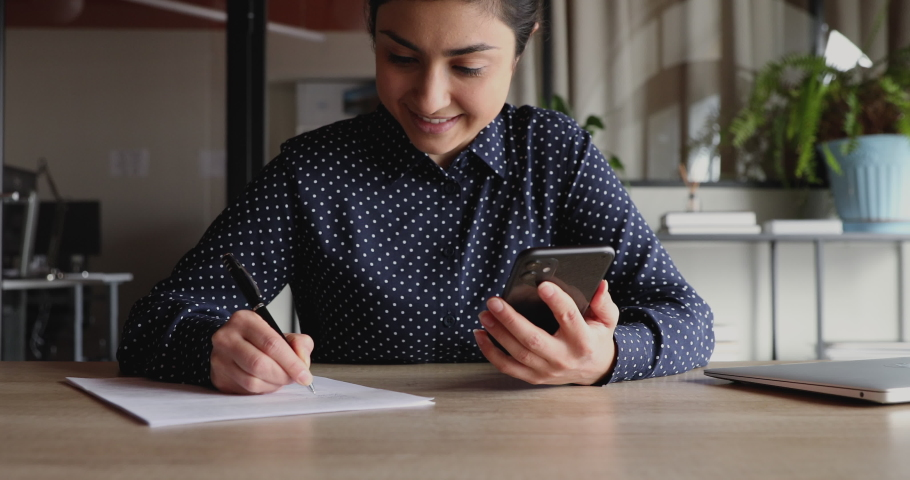 Smiling young indian woman student worker holding smartphone, making notes working studying from home office. Happy businesswoman looking at phone using app for business planning, distance learning. Royalty-Free Stock Footage #1049816965