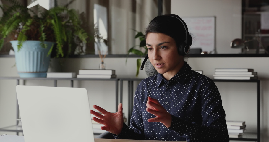 Confident indian female web coach, online teacher or customer support service operator wearing headset speaking to webcam looking at laptop. Ethnic business woman making conference video call concept. Royalty-Free Stock Footage #1049816968