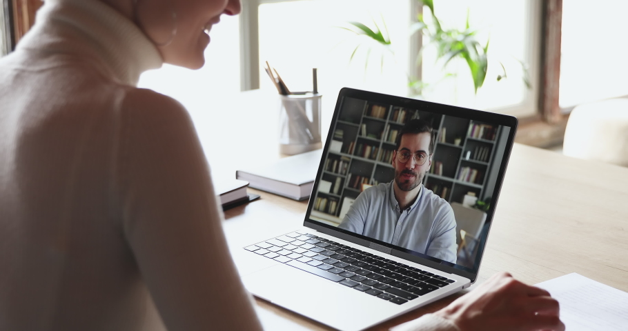 Over shoulder view of woman student worker makes conference video call on laptop talks with online teacher, boss or partner in web cam chat on computer screen. Distance work, remote education concept. Royalty-Free Stock Footage #1049816977