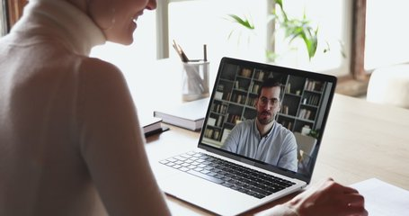 Over shoulder view of woman student worker makes conference video call on laptop talks with online teacher, boss or partner in web cam chat on computer screen. Distance work, remote education concept.