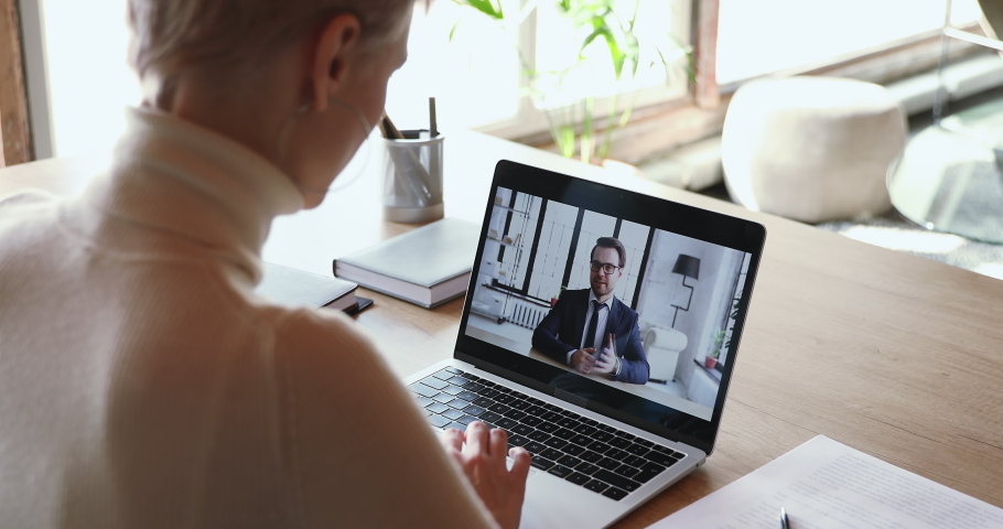 Male boss conference calling distance worker in corporate webcam video chat app. Female applicant communicating with employer during remote job interview concept. Over shoulder close up screen view. Royalty-Free Stock Footage #1049816980